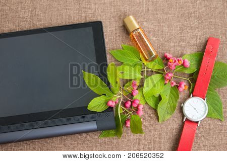 Tablet Computer With Flowering Branch, Wrist Watch And Perfumes.