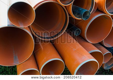 Stack of pvc pipes on a construction site.