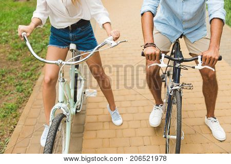 cropped shot of couple holding hands on bicycle handle bars in park