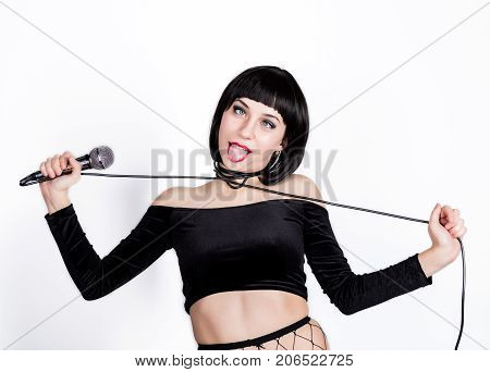 eccentric girl strangles herself with a cord from a microphone. on a white background