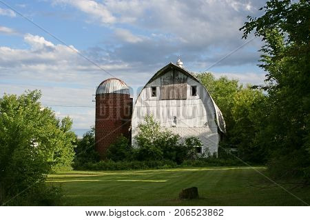 A disused red silo and white barn on a farm.