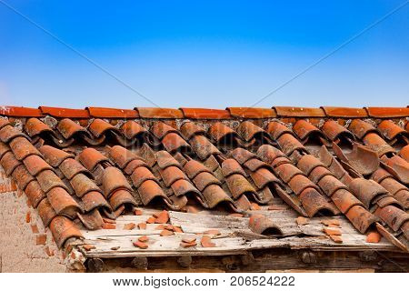 Broken brick on the roof of a cottage. Damaged roof.