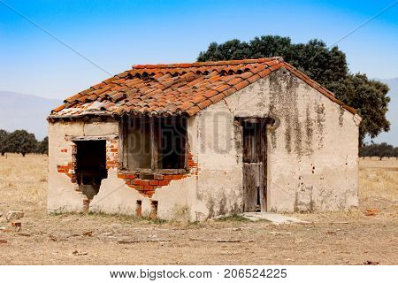 Small old house with the roof collapsed and a broken window