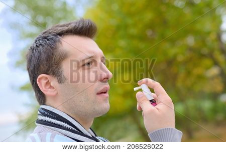 Man spraying with nasal spray in autumn time