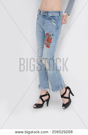 Fashion. Woman legs in embroidered flowers and black high heels shoes posing in studio