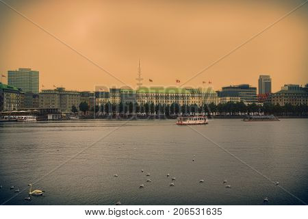 HAMBURG GERMANY - AUGUST 22 2016: Panoramic view of The central lake Binnenalster (Inner Alster Lake). Clouds over the modern city and the second largest city in Hamburg Germany on August 22 2016.