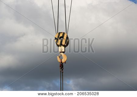 Hook Big Gantry Crane Made Of Metal Colored Yellow Against A Background Of Bright Blue Sky With Clou