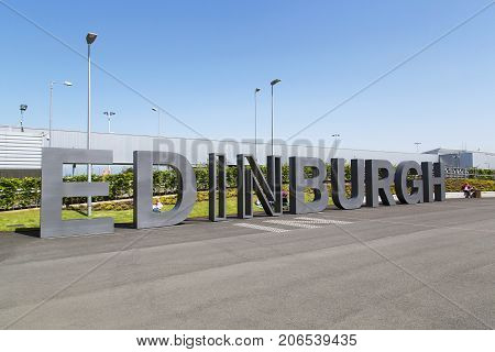 Edinburgh, UK: May 29, 2016: Families wait for planes to arrive outside the main entrance to Edinburgh Airport. Edinburgh Airport is located at Ingliston in the City of Edinburgh.