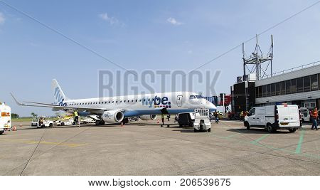 Cardiff, UK: May 29, 2016: A landed aircraft is being serviced by the ground crew while passengers still desembark. Flybe is the largest independent regional airline in Europe and is based in Exeter.