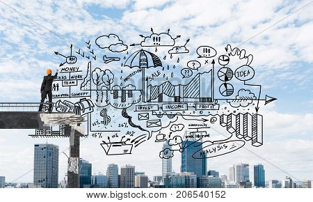 Businessman in helmet drawing business-analytical strategy while standing on broken bridge with cityscape on background. 3D rendering.