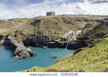 Tintagel, Cornwall, UK: April, 2016: A view of the main entrance to Tintagel Castle in the valley and Hotel Camelot on the cliff. There is a beach cafe, visitors centre at the entrance.