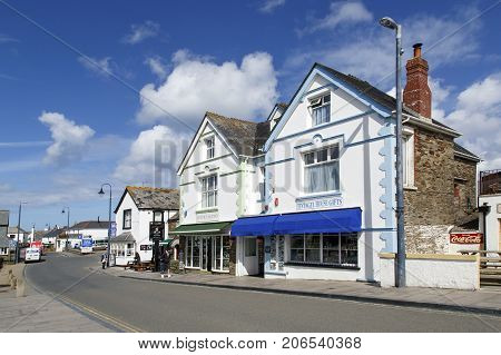 Tintagel, Cornwall, UK: April 14, 2016: Street view of the popular tourist village of Tintagel in Cornwall. There are gift shops and a pub with two people walking through the village.