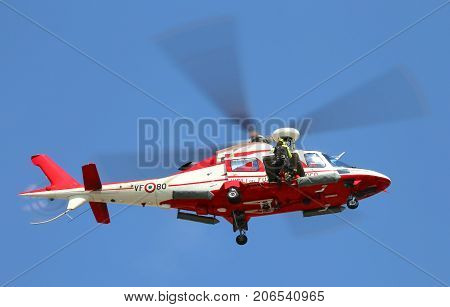 Veneto, Italy - May 26, 2016: Helicopter Of Italian Fire Brigade With A Fireman Leaving The Door Dur