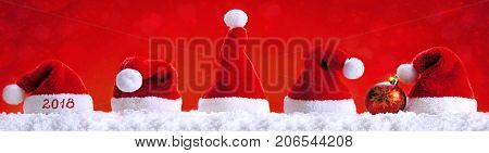 Five red santa hats isolated on red background.Christmas red background with Santa hats.Happy new year 2018 santa hats.