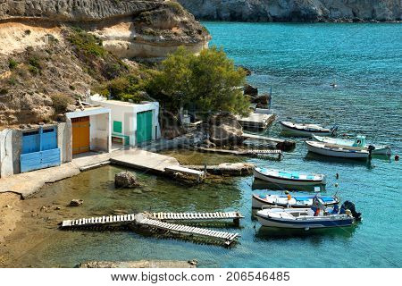 Fishing boats floating on turquoise water at Mandrakia in Milos Island in Cyclades in Greece