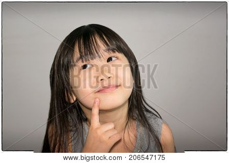 Intelligent Asian Child Actively Brainstorming New Ideas
