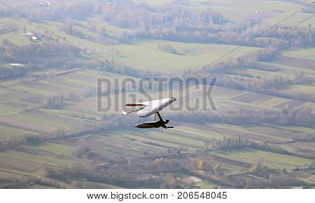Man Flying With Hang Glider Above The Plain. This Is Extreme Spo