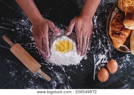 Raw dough for bread with ingredients on black background male hands kneading dough sprinkled with flour table.