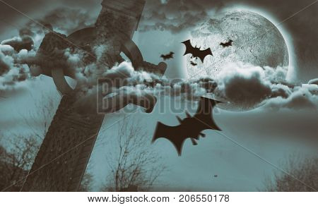 Digital image of silhouette bat against celtic cross in front of moon behind clouds