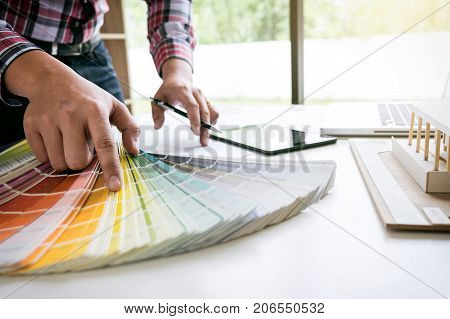interior design or graphic designer working on project of architecture drawing with work tools and color swatches colour chart in digital tablet at workplace.