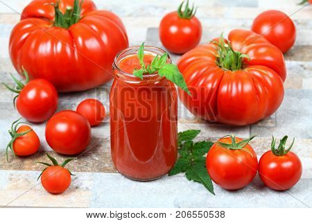 Homemade preserved ketchup from giant beefsteak cherry and common tomatoes in a bottle. Fresh tomatoes are around a bottle tomato leaf is in a ketchup.