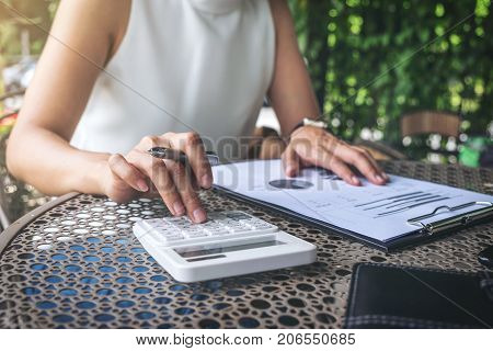 Work and relax Woman freelancer is working new project of business stragegy plan and using calculator to analysis information data while sitting garden scenery outdoor background.