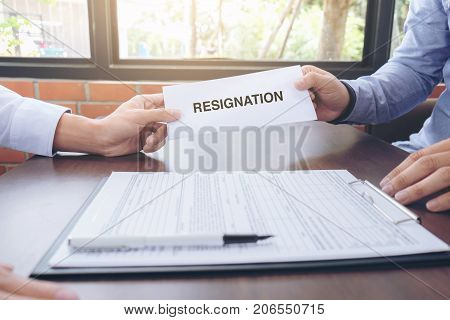 Close up of the hand employer filing final remuneration after employee to write a document letter of resignation resign concept.