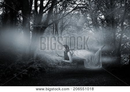 Full length of woman levitating  against way between trees