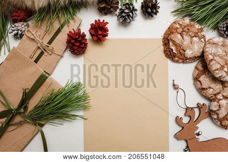 Festive presents for Christmas and New Year. Top view clean piece of paper, wrapped gifts, decoration and sweet cakes. Congratulation, greeting card, letters and home baking concept