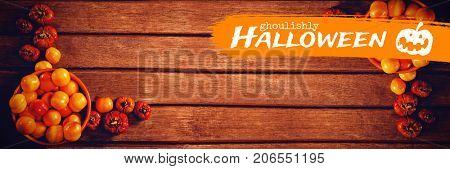 Graphic image of ghoulishly Halloween text against candies with small pumpkins on wooden table