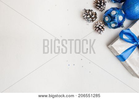Festive background of Christmas decor and gifts. Wrapped present, ornament blue balls and strobila laying on white table, top view with copy space. Congratulation and handmade decoration concept