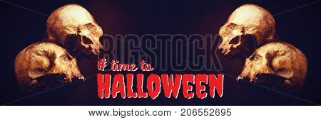 Digital composite image of time to Halloween text against high angle view of human skulls