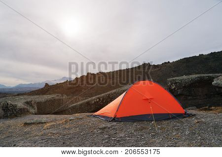 An orange high-altitude tent is set between stones high in the mountains of the Caucasus against the backdrop of the Caucasian ridge. Glade of stone mushrooms on Mount Elbrus