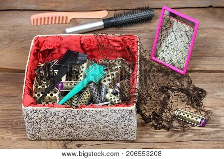 Ancient hairdresser set with hair curlers razor blades mirror comb and hair net. Barber set in a luxury box on wooden table. Hairdo kit from last century.
