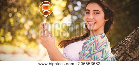 Digital composite image of bus icon on green circle against portrait of smiling woman using phone