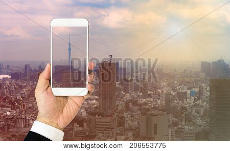 Tokyo rooftop view : Handholding smartphone over Tokyo cityscape background.