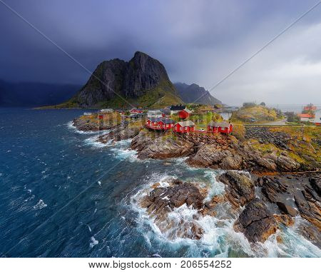 Norwegian fishing village Reine on the Lofoten islands. Red norwegian rorbu houses on stone coastline. Nordic nature at stormy weather. Blue sea waves near norwegian fishing village.