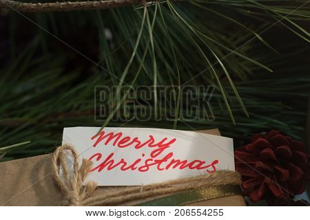 Festive background of Merry Christmas greeting. Close up handmade striped package with memo on pine branch backdrop. Presents, New Year traditions and congratulation concept