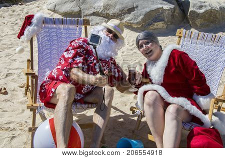 Santa And Mrs Claus Taking Selfie With Stick On Beach