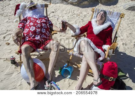 Santa And Mrs Claus Sharing A Tropical Cocktail On The Beach