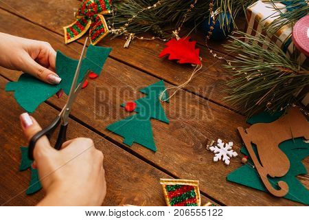 Holiday preparation. Christmas and New Year. Unrecognizable woman scissors out green felt fir tree on wooden background, festive home decoration concept. View from shoulder