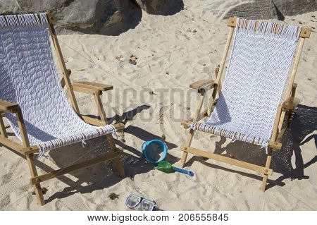 Empty beach chairs with toys on sandy seashore.