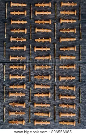 Dowels lying in rhythm on dark wooden background