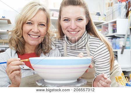 Portrait Of Mature Woman Decorating Bowl With Teacher In Pottery Class
