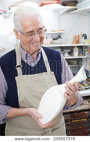 Senior Man Holding Vase In Pottery Studio