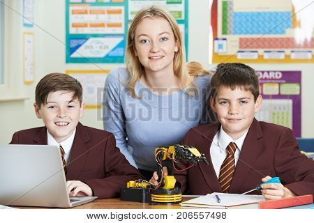Portrait Of Teacher With Pupils In Science Lesson Studying Robotics