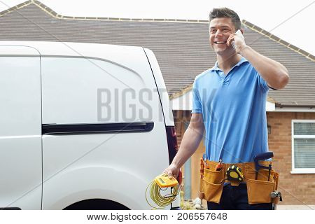 Electrician Standing Next To Van Talking On Mobile Phone