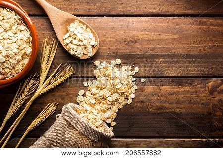 Oat Flakes, Uncooked Oats In Bowl With Wooden Spoon And Wheat Ears. Negative Space