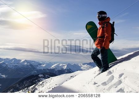 Small snowboarder on blue sky backdrop. Snowboarding space for text concept
