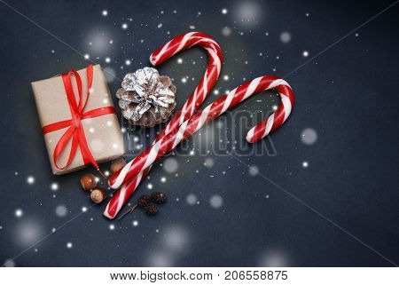 Christmas candy and gift box with red bow, green fir tree, snowflake on blue background. Christmas background. Top view and copy space. Christmas concept.